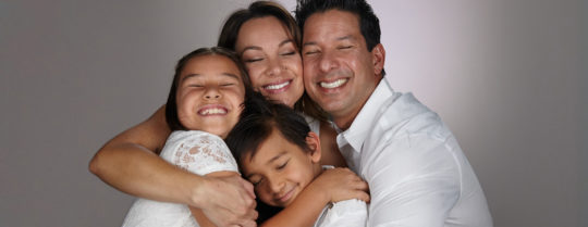 Family of four hugging with eyes closed and smiling.