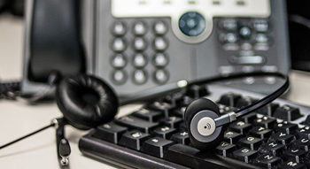 Photo of a telephone, keyboard, and headset representing the Hawaii State FCU Member Service Branch