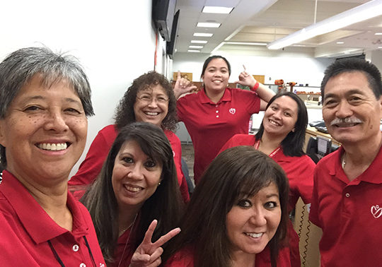 staff members in red shirt goofing off and smiling