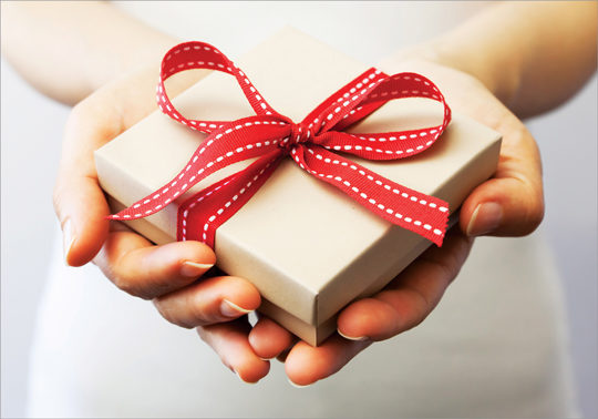 Holiday promo image of hands with a gift.