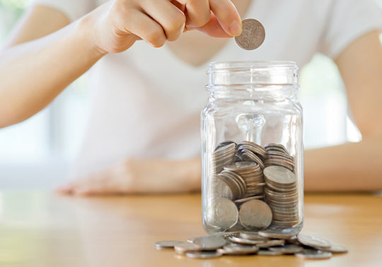 Close up photo of a woman putting coins in a clear mason jar filled half way with coins
