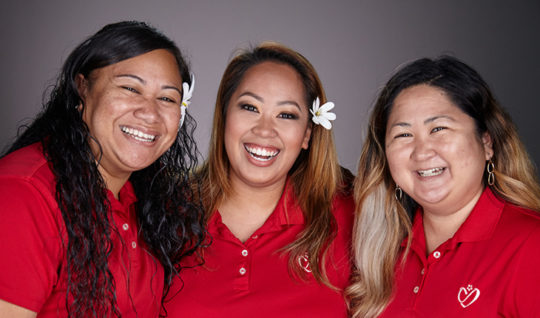 Three Hawaii State FCU employees in red shirts smiling.