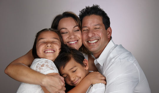 smiling family doing a group hug