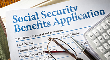 Social Security Benefits form with pen, glasses, and calculator