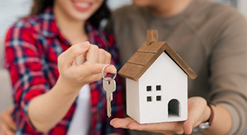 couple holding house and key
