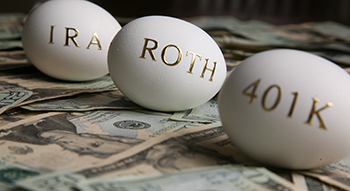 Three eggs with gold writing (IRA, ROTH and 401K) on top of bills