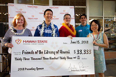 Andrew Rosen, center in red shirt, poses for a picture with leaders from Friends of the Library of Hawaii with a big check showing Hawaii State FCU's donation of $33,333. Hawaii State FCU was the 2018 presenting sponsor.