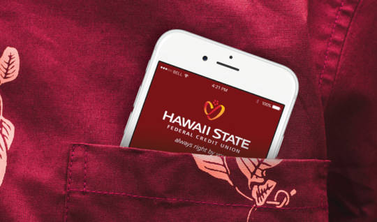Mobile Phone with the Hawaii State FCU Mobile App in the pocket of a aloha shirt.