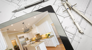 Home renovation plans and ipad with photo of a remodeled kitchen