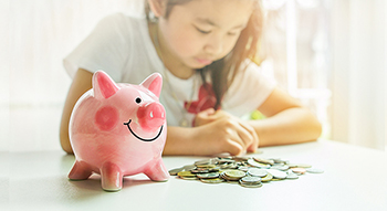 piggy bank and pile of coins on table with background of little girl