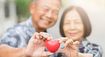 Older Asian couple holding a heart