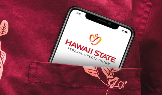 Red aloha shirt with a smartphone in the shirt pocket. The screen on the phone displays the Hawaii State FCU logo. This image conveys the idea that you can do banking on the go. Mobile. Like you.