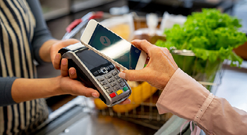 Photo of a person tapping their iPhone to the digital reader to pay for their groceries at the checkout counter.