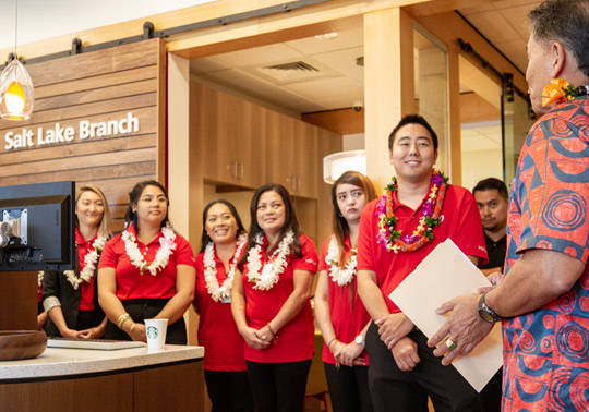 Photo of the Salt Lake Branch team wearing red HSFCU polo shirts and lei.