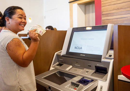 Photo of a member holding cash after using the ITM machine at the Salt Lake Branch.