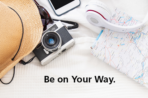Photo of hat, camera, phone, headphones, and map with text,
