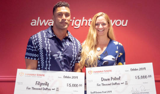 2019 Small Business Grant Winners, Brad Kalilimoku of Fitgevity and Dawn Martin of Dawn Patrol Assesments with their checks in the amount of $5,000 each.