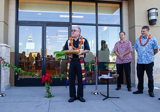 Photo of the Reverend holding ti leaf and koa bowl infront of the front doors of the new Ewa Beach Branch, preparing to bless the branch and employees.