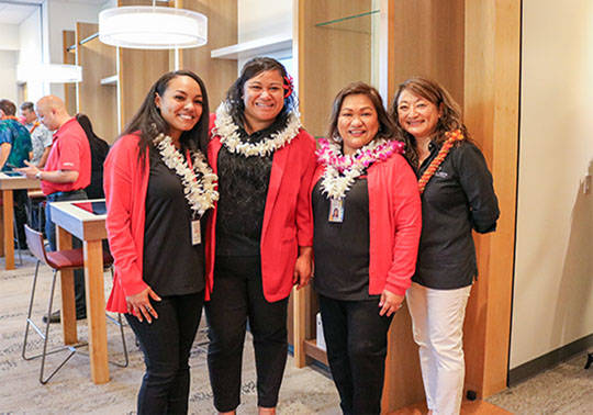 Photo of HSFCU employees wearing lei, smiling and posing inside the new Ewa Beach Branch.