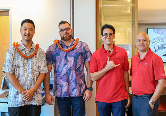 A photo of a group of HSFCU male employees and two other guests wearing lei, posing and smiling inside the new Ewa Beach Branch on opening day.