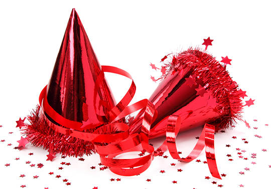 Photo of two red metallic party hats with red ribbon and confetti