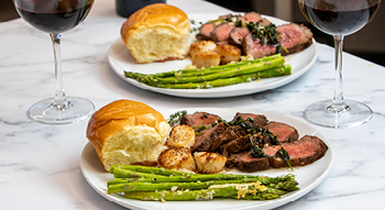 A photo of the Bites on a Budget Surf and Turf meal which includes steak, scallops, sweetbread roll and asparagus.