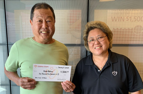 Photo of HSFCU 2019 Q4 Refer a Friend winner, Kevin Nakaue, left, receiving his $1,500 check from Kaimuki Branch manager, Kathy Ishiro, right.