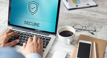 Photo of a man on a laptop with a shield icon and the word secure on the screen.