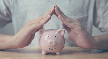 A photo of a person whose hands are positioned like a house over a pink piggy bank as if protecting it.
