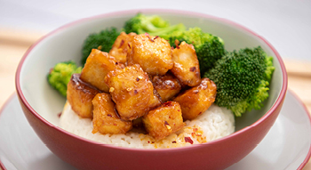 Photo of a bowl with our Bites on a Budget Firecracker Tofu and steamed broccoli on a bed of white rice.