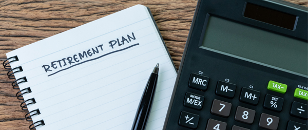 A photo of a notepad with Retirement Plan on it next to a pen and calculator.
