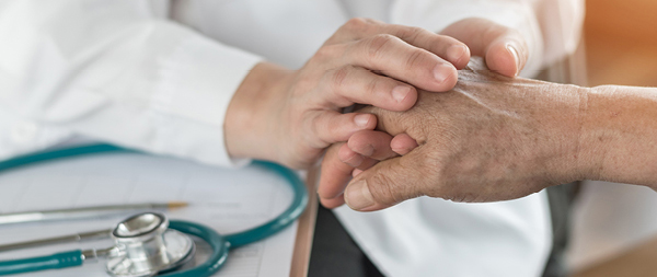 Photo of a nurse holding the hand of a senior citizen.