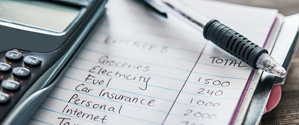 Photo of a calculator next to a pen and a handwritten budget on a notepad.