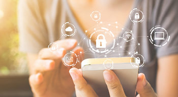 Photo of a person holding a smartphone with an illustration of a network of icons representing cloud storage, email, laptop and mobile security icons.