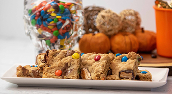 A photo of a plate of homemade leftover Halloween candy bar cookies.