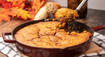A photo of a scoop of cornbread chili pie being served from the pan ready to eat for the Thanksgiving holidays.