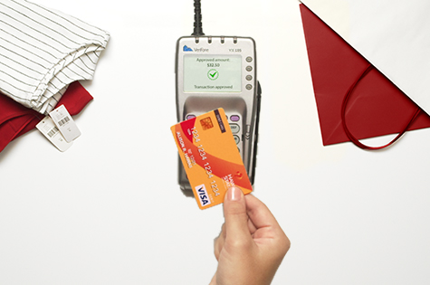 An aerial view photo of a credit card hovering over a card reader to purchase items at a store.