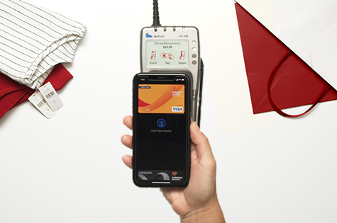 An aerial view photo of a debit card loaded into digital wallet on a smartphone that is hovering over a card reader to purchase items at a store.