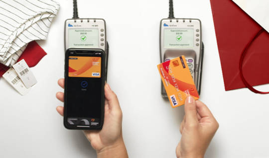 A photo of a person holding their smartphone using their credit card loaded in their digital wallet over the card reader to pay for their purchase. Another person holds their contactless credit card over the card reader to pay for their purchase.