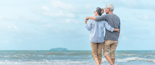 A senior couple standing on the beach looking at the ocean waves.