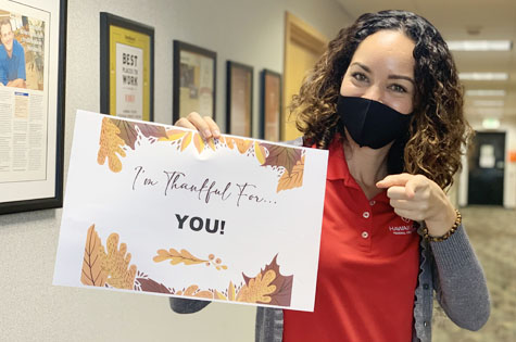 A photo of a HSFCU employee holding a sign that says I'm thankful for YOU.