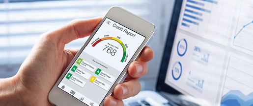 A close up photo of a person holding their smartphone displaying their credit report and credit score.