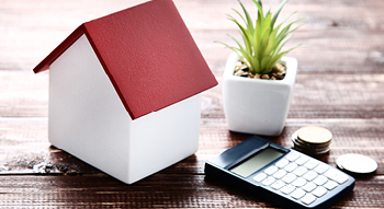 A miniature white house with a red roof sitting on a table with a plant, calculator and stacks of coins to convey home equity line of credit.