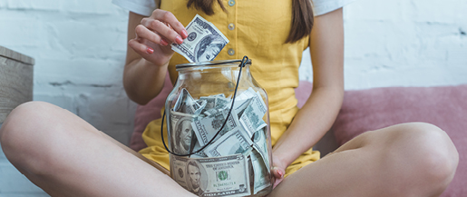 An image of a teenage girl saving her money in a big glass jar.