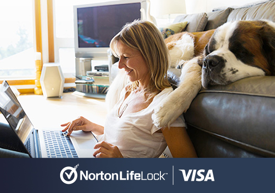NortonLifeLock & VISA logos with image of a woman using her laptop and dog lying on a couch behind her