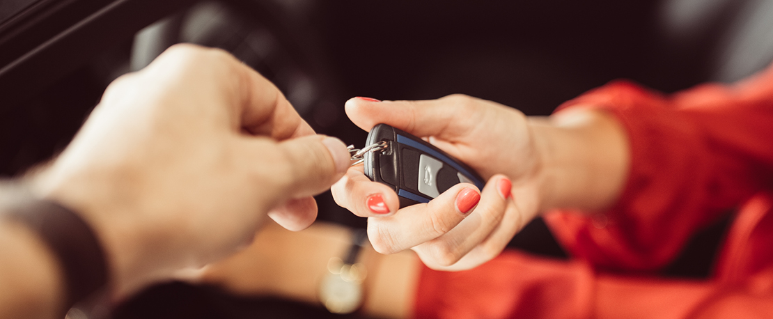 Photo of two people handing over car keys.