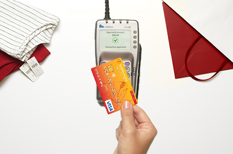 HSFCU Visa<sup>®</sup> Contactless Credit Card being tapped over a credit card reader