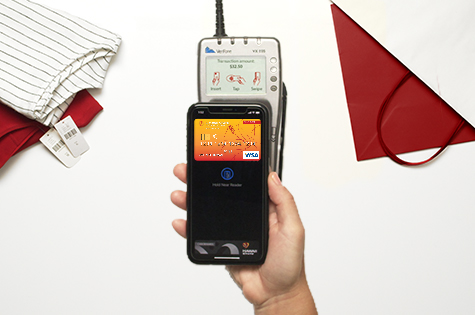 HSFCU Visa<sup>®</sup> Credit Card loaded into a digital wallet on a smartphone hovering over a credit card reader