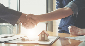 People shaking hands after buying a home