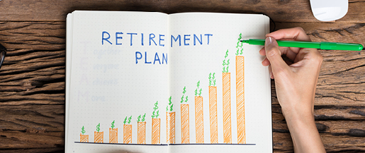 An image of a notebook with the words Retirement Plan and a bar graph drawing open on a desk.